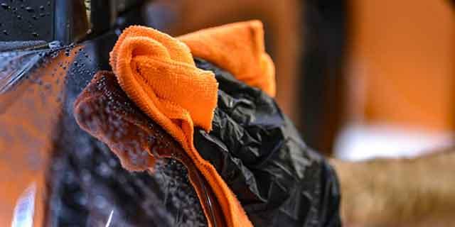 Autowäsche, Hand mit orangenen Schwamm auf schwarzem Auto