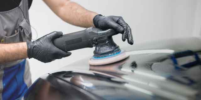 Mann poliert Autohaube mit Poliermaschine
