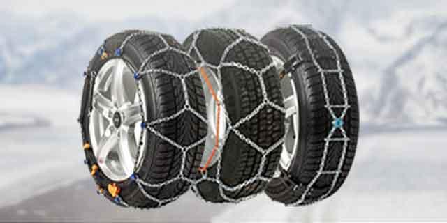 Reifen mit Schneeketten vor verschneiten Bergen