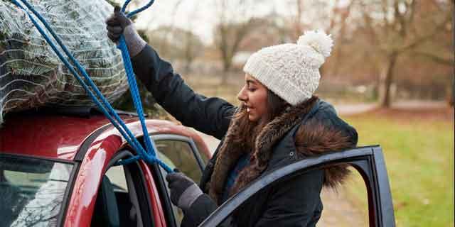 Frau schnürt Weihnachtsbaum mit Zurrgurt an Autodach fest